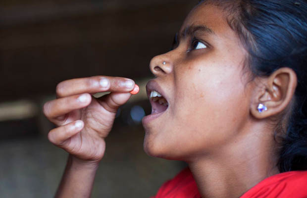 Adolescent girl consuming iron tablet